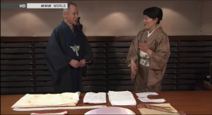 Screenshot from the video showing Japanese woman explaining Kimono practices to a the host of the show.