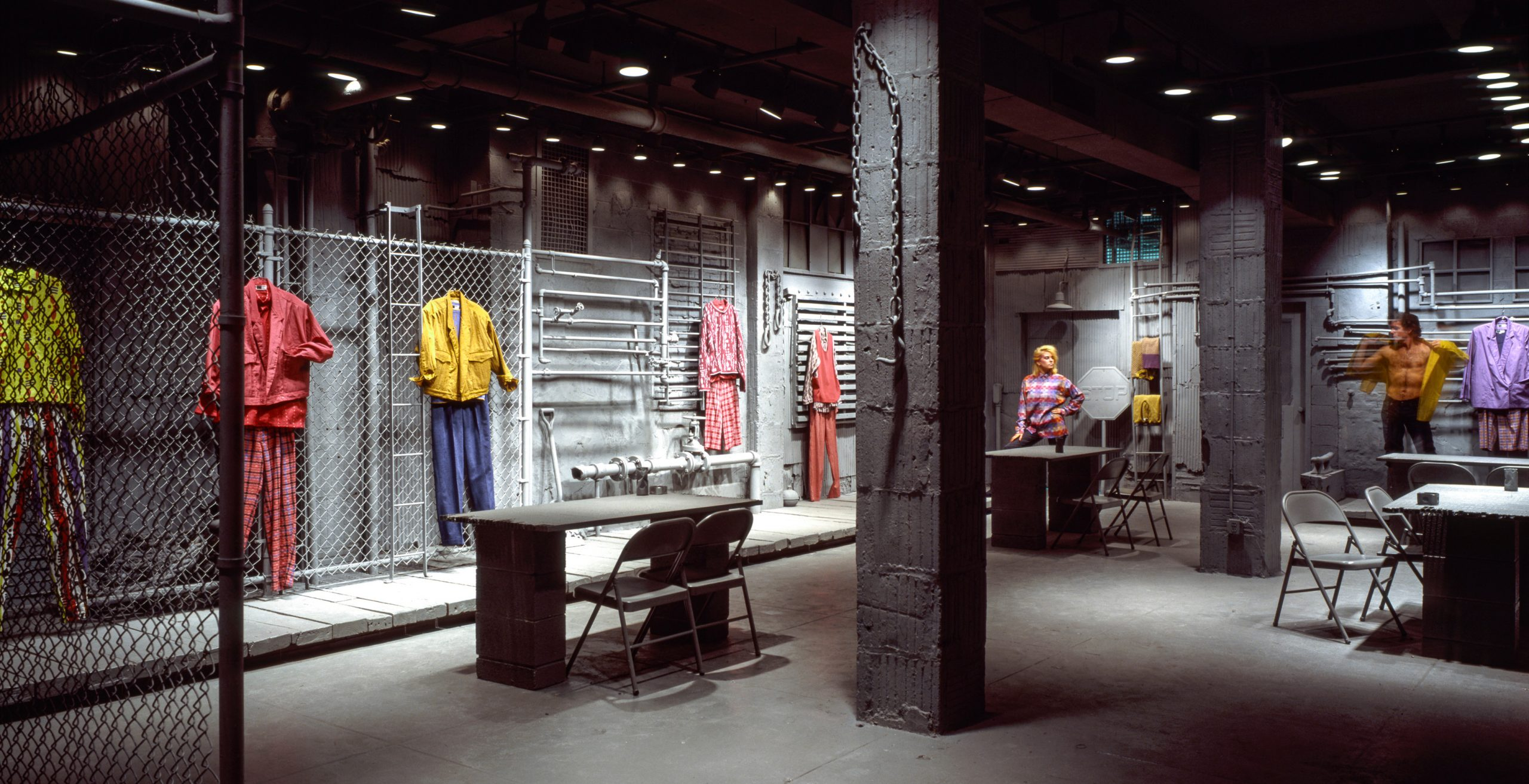 Exhibition showroom for WilliWear featuring looks hung on the walls of an industrial set