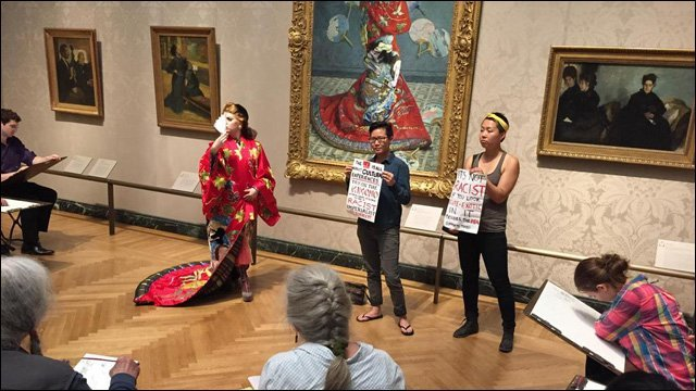 two protestors stand with signs in front of framed piece of art in a museum, as a group of spectators looks on