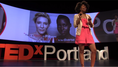 Still image from the talk of Amber Starks speaking on the TEDx stage