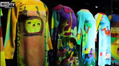 Screenshot from the video of several colorful printed Ao Dai on display in a museum