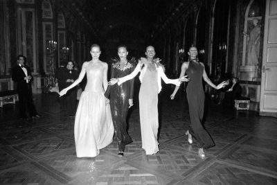 black and white photo of 4 models walking the halls of versaille