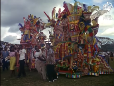 Still image from the archival footage of two large floats being pulled into the Carnival parade