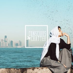 Image of Hoda Katebi sitting on the shoreline of a city with the Conscious Chatter logo in the middle of the photo