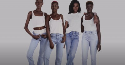 Image of 4 darkskin models in light wash jeans and white tops posing together in front of a white background