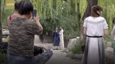 Screenshot from the video of some people taking photos of two young women dressed in Hanfu style clothing