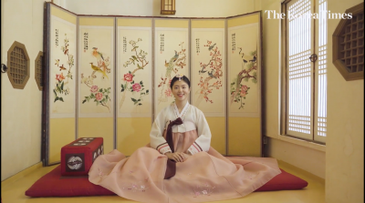 Screenshot from the video of a Korea Times reporter dressed in a pink and white Hanbok seated on the ground