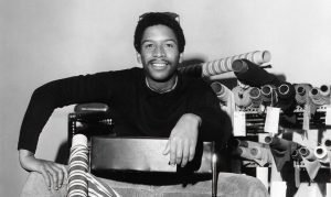 Black and white photograph of Jay Jaxon sitting on a chair in front of several rolls of fabric