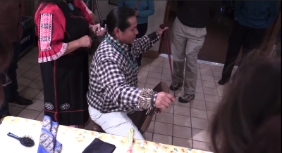 Screenshot from the recorded lecture of a Southwestern Native American Man getting his hair tied