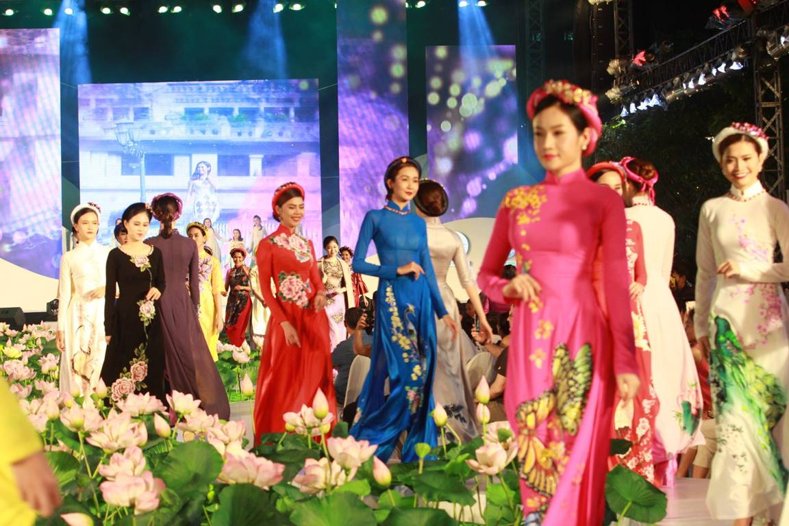 Several models walking up and down the runway in different styles of Ao Dai