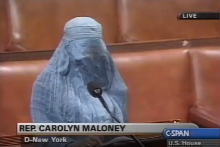 Rep. Carolyn Maloney stands before a mic in a blue burka.
