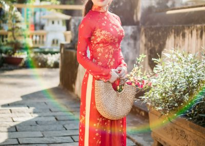 Image of a young woman in a red Ao Dai standing one a stone walkway in a garden.