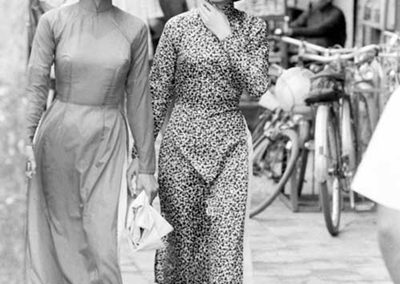 A black and white photo from the 1960s showing two women in the streets of Saigon dressed in Ao Dai
