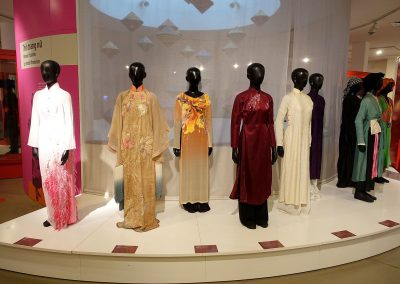 A museum display of several mannequins wearing different styles of Ao Dai