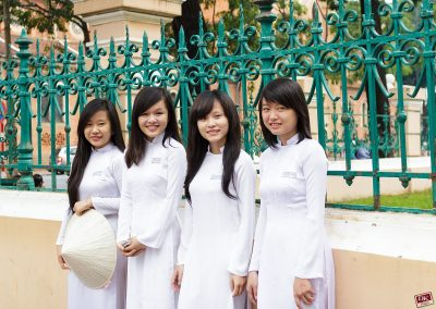 4 young female students wearing white Ao Dai in front of a green iron gate