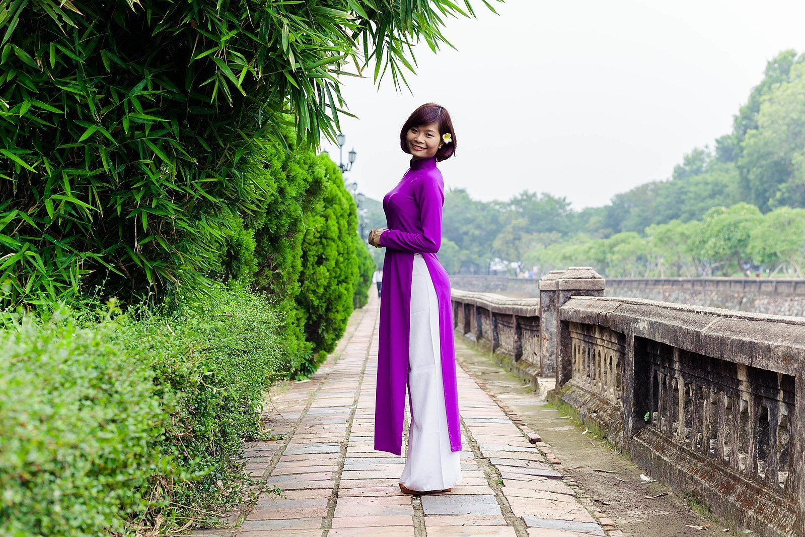 Image of a woman in a purple Ao Dai worn over white trousers