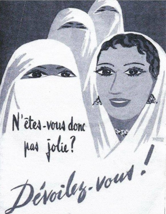 """Black and white scan of French Colonial Poster reading """"N'êtes-vous donc pas jolie? Dévoilez-vous! ››/""""Are you not pretty? Unveil Yourself!"""". Two women in the background are wearing white veils. There are two women in the foreground. The one on the left wear a white veil, only her eyes visible. The woman on the right wears a headscarf with some hair and earrings exposed, makeup and a smile on her face."""