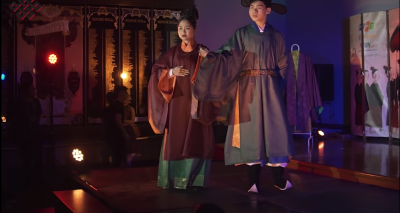 Screenshot from the video of two models on stage in ancient vietnamese costumes