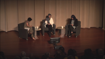 Still image of the three speakers sitting on stage