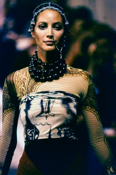 A model walking down the runway covered in sheer clothing with tattoo patterns on it