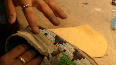 Screenshot from the video of Teri Greeves working on beading the upper sole of the moccasin