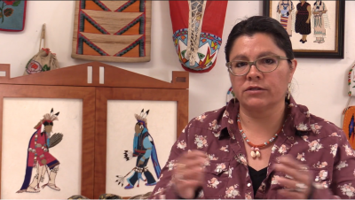 Screenshot from the video of Teri Greeves speaking in front of a wall of her work