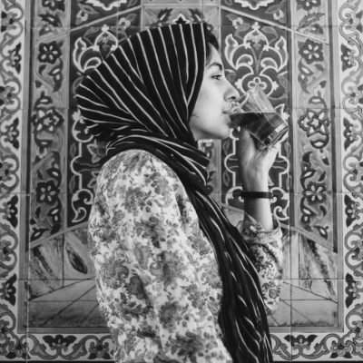 Black and white portrait photo of Hoda Katebi in profile, facing right as she sips a glass of chai.