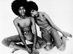 A black and white photo of a black male and female models with afros