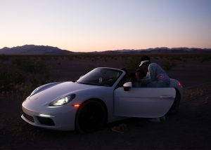 1 crew member sitting in the driver seat of a 2 door white Porshe Boxter with the headlights on and the driver door open as the 2nd crew member stands talking to the 1st. The car is parked with the desert with minimal green brush and low mountains in the background. The light from the sun is quickly fading as the pink of the sunset is disappearing.