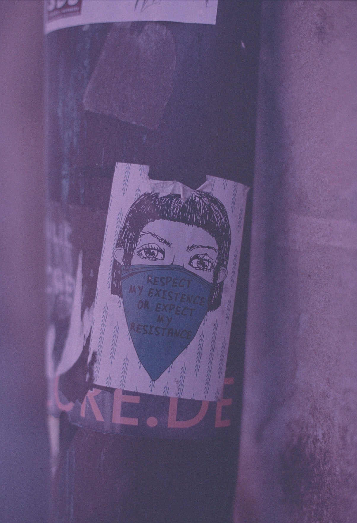 a purple-tinged photograph of a protest poster pinned to a lamp post
