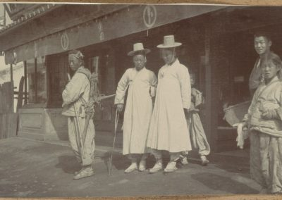 Vintage black and white photo of 7 Koreans in traditional dress. 2 men in white Hanboks.