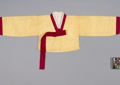 Photo of Hanbok jacket. Yellow canvas, and red cuffs and collar and tie.