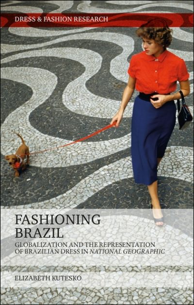 Person in a red button-front shirt and navy pencil skirt walking a small dog on a red leash