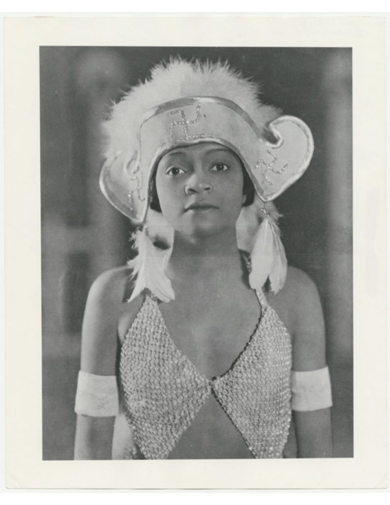 Black and white portrait of showgirl in small feather headdress