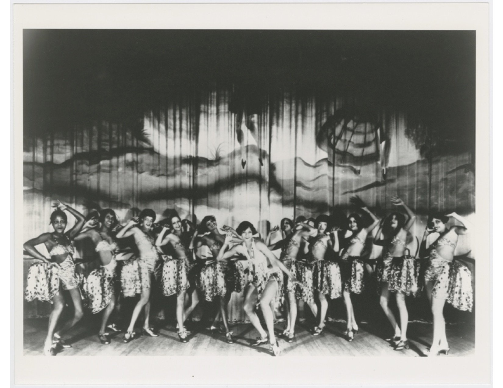 Black and white photo of 11 showgirls on stage