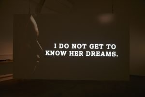 "Text reading ""I do not get to know her dreams"" projected onto a screen. There is a silhouette of a face on the left hand side of the screen."