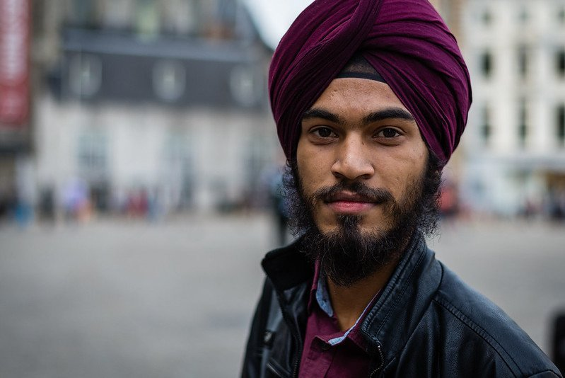 Sikh man with purple dastaar (sikh turban wearing leather jacket and purple shirt.