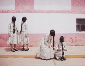 Four people with dresses and hair braided in front of their faces
