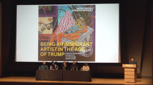 Still image from the recorded lecture of the 5 panelists sitting on stage in front of a large screen with the event poster projected on it