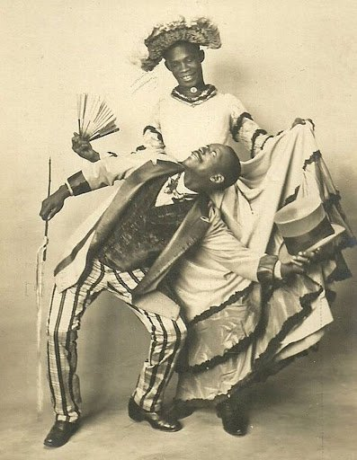 aged photograph showing two black actors, one in drag, dancing the Cake-Walk