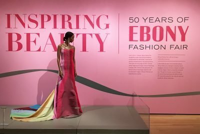Photo of exhibition gallery with title and description and a dark-coloured mannequin with a dress in shades of pink and yellow