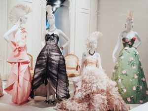 "Gallery view of the exhibition ""Oscar de la Renta: The Retrospective"" with four mannequins dressed in pastel colours"