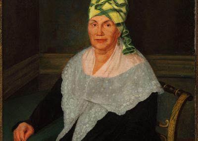 woman in a green and yellow madras tignon