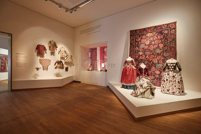 Exhibition gallery with garments and textile hangings made with printed cotton