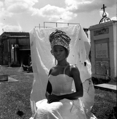 Woman seated outside in front of a white sheet wearing a headwrap