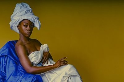 Seated woman against yellow background wearing a headwrap