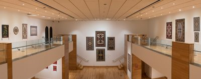 Gallery view with Navajo textile hangings on the walls