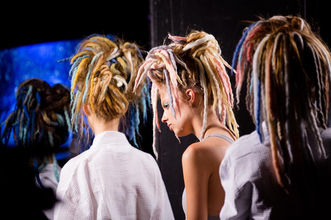 three runway models with their hair arranged in multi-colored dredlocks