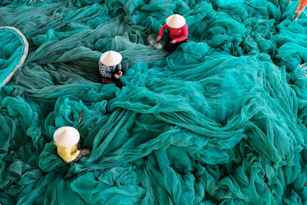Three women sit amidst an enormous pile of a billowy turquoise fabric