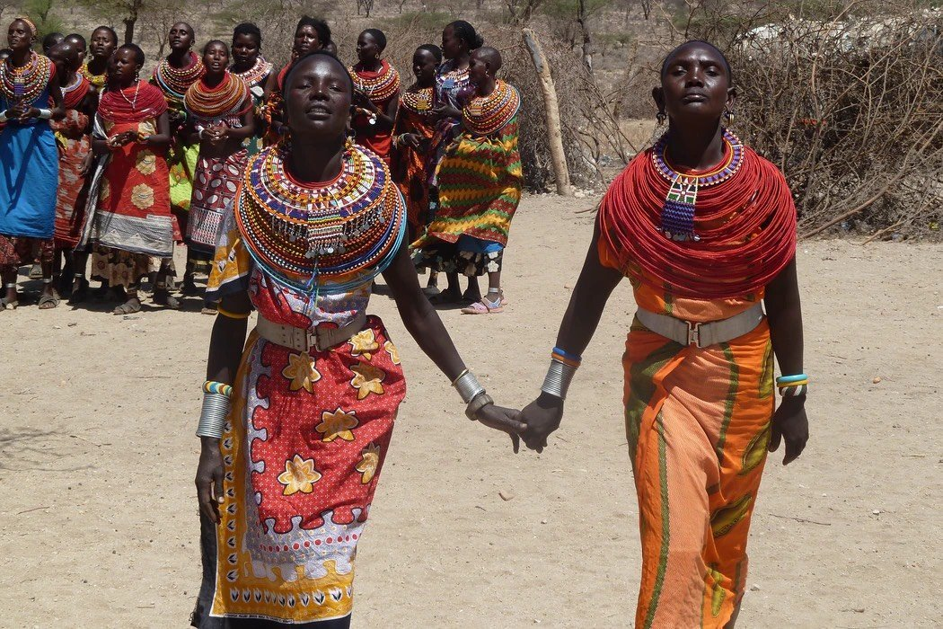 two women in the foreground clasp hands, while some 9 other women stand in the background. All are dressed in vibrant colors.